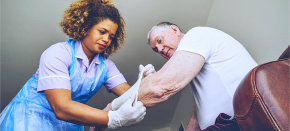 Nurse putting a bandage on a senior man's arm