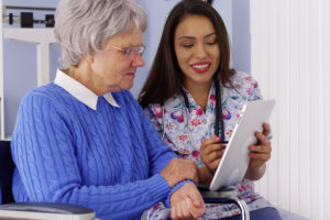 caregiver sharing tablet with elderly patient